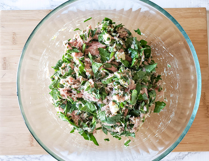 turkey mixed with spinach and cheese in a bowl
