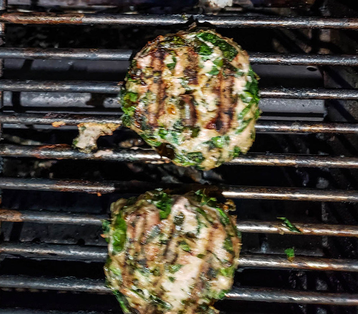 two burgers cooking on the grill