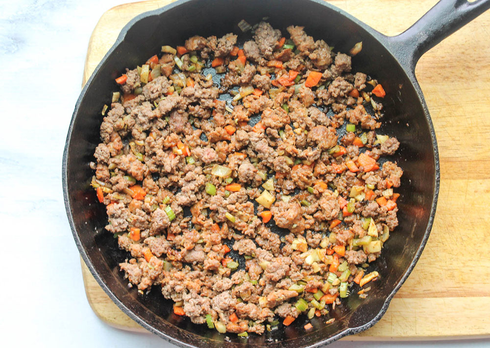 cooked ground meat and vegetables in a skillet