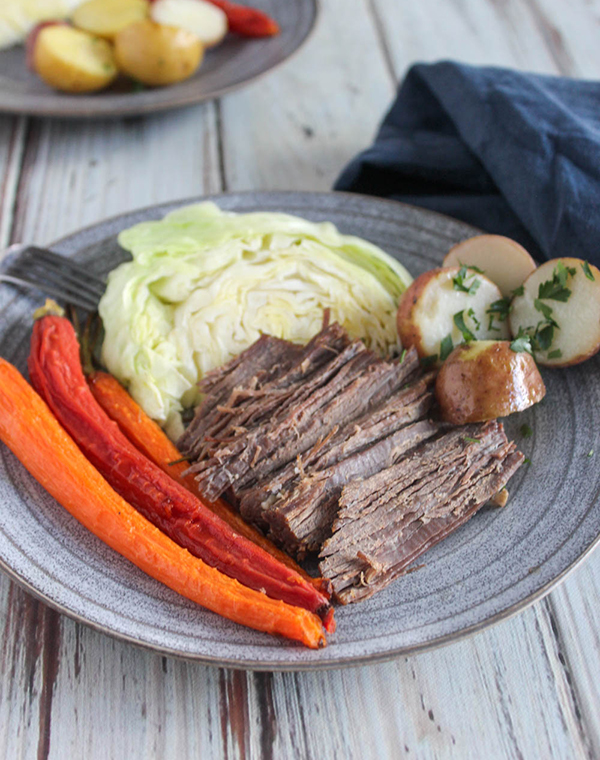corned beef brisket on a blue plate with carrots potatoes and cabbage