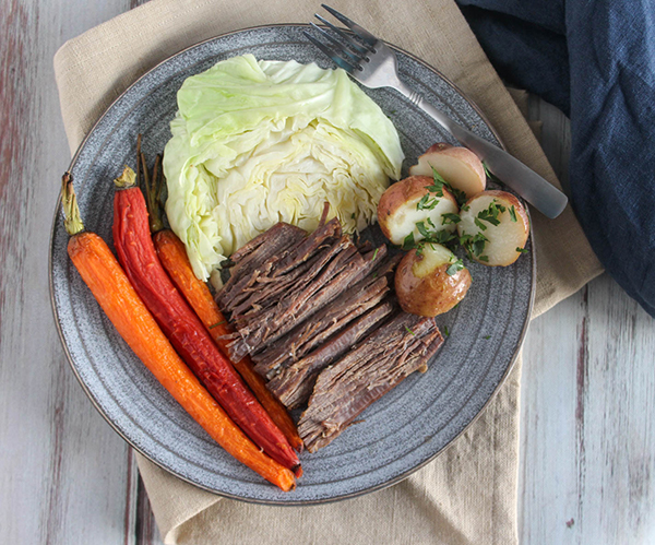 corned beef and cabbage on a plate with carrots and potatoes