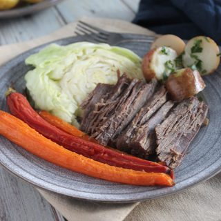 carrots corned beef cabbage and potatoes on a plate with a fork