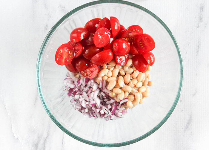 an overhead view of beans, onions and tomatoes in a bowl