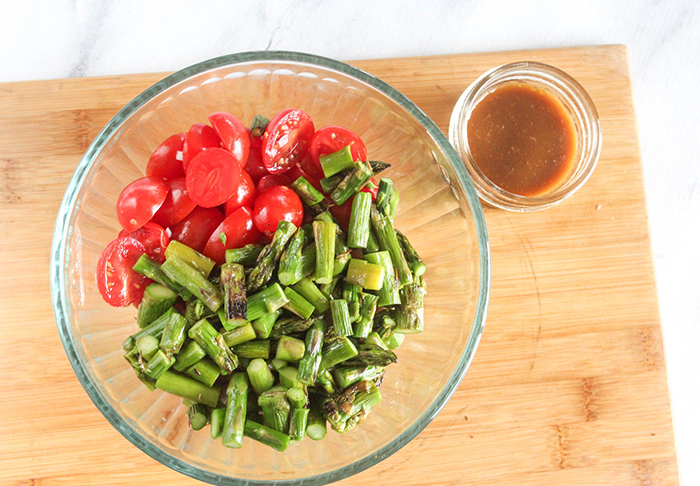tomatoes and asparagus in a bowl with dressing on the side