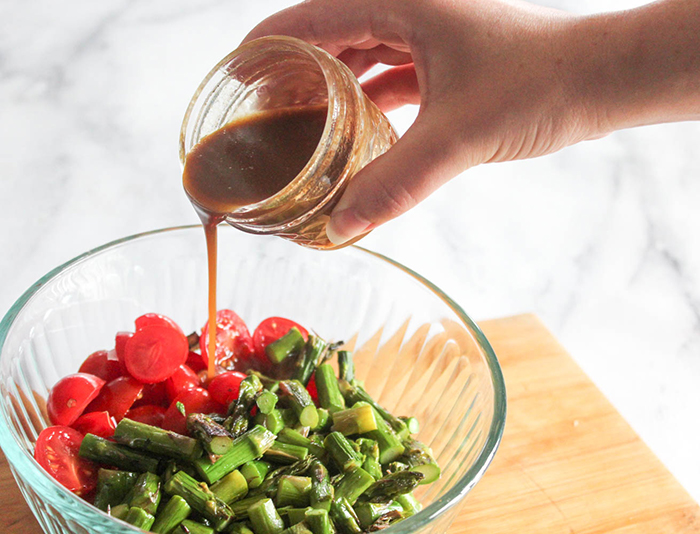salad ingredients ina bowl with dressing pouring in