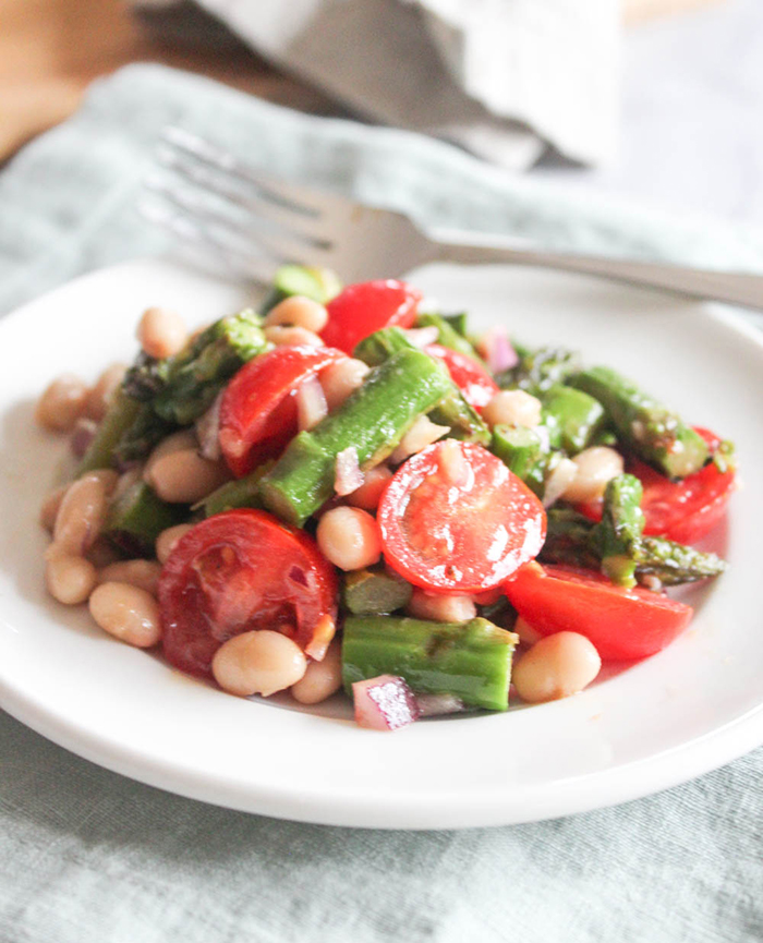 asparagus salad with tomatoes beans in a white dish