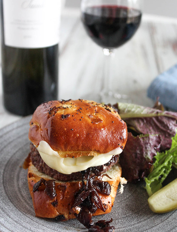 Caramelized onion burger in a roll with a glass of red wine on the side