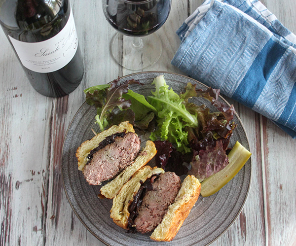 caramelized onion burger cut in half on a plate with a salad
