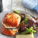 caramelized onion burger on a plate with pickles and a salae