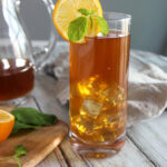 Iced tea in a glass with a pitcher in the background