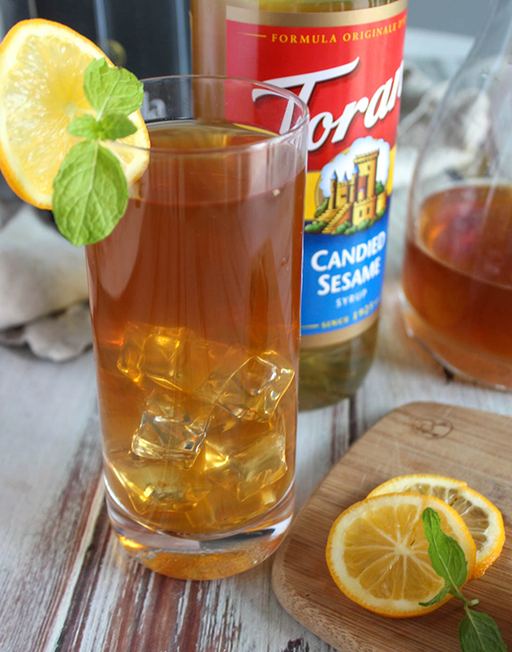Sesame ginger iced tea in a glass with lemon slices