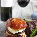 caramelized onion burger on a plate with a salad