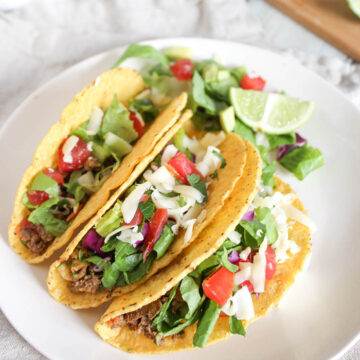 three tacos on plate with lime and lettuce