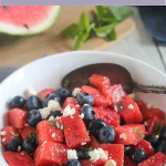 Red White and blue salad in a white bowl with a spoon