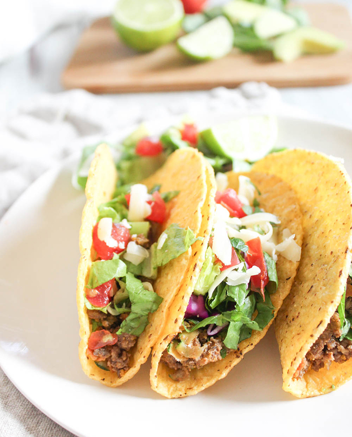 three tacos on a plate with lettuce tomatoes and shredded cheese