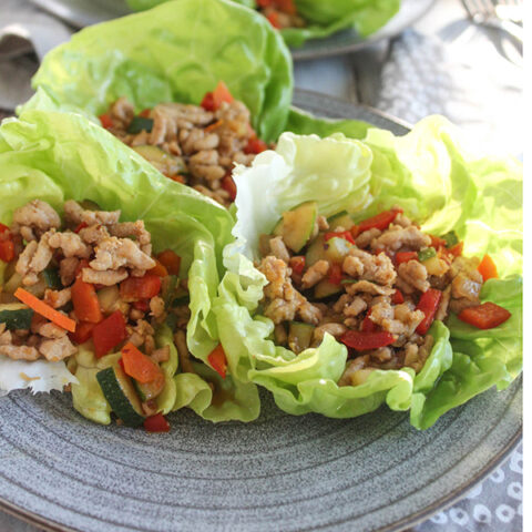 Three Asian chicken lettuce wraps on a plate