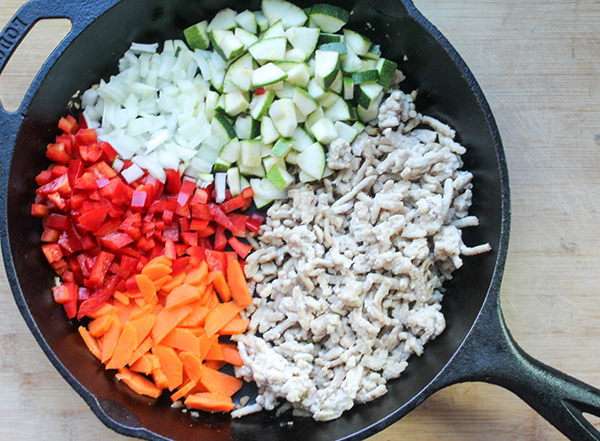 diced carrots peppers onions and zucchini in a pan
