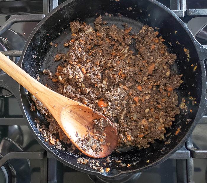 Processed veggie burger ingredients cooking in a skillet