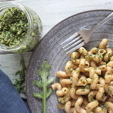arugula pesto on a plate with a jar of pesto sauce on the side
