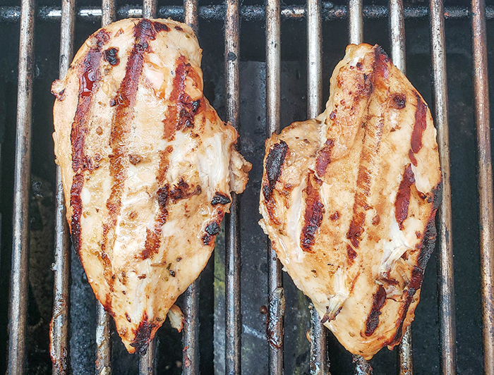 chicken breasts cooking on the grill
