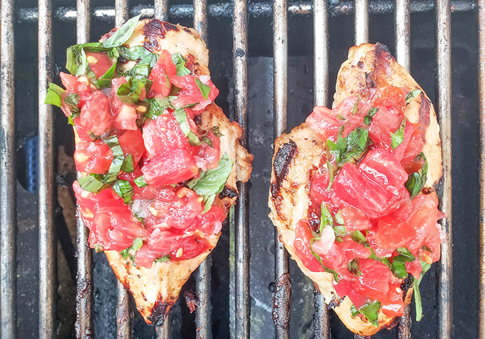 chicken breasts on grill with tomatoes