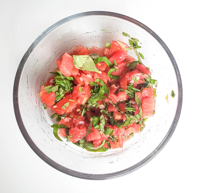 an overhead view of tomatoes and basil mixture in a bowl