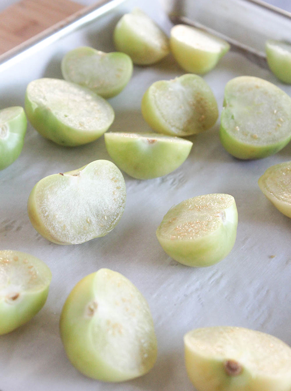 tomatillos sliced and arranged on a baking sheet