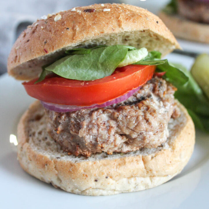 caribbean jerk chicken burger on a roll with lettuce and tomato on top
