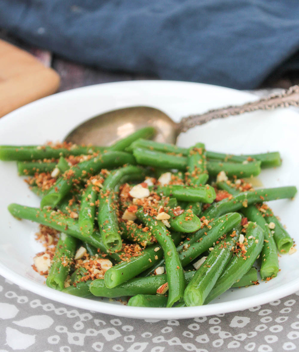 Green beans in a serving bowl topped with bread crumbs and almonds