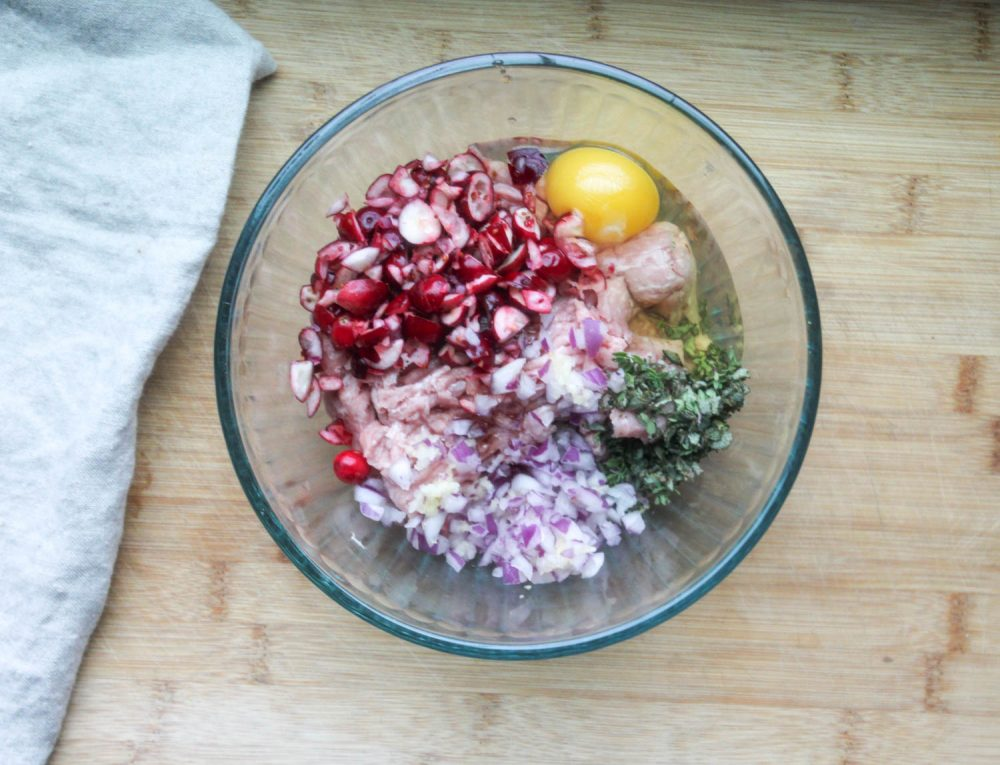 chopped cranberries, egg, onions ground turkey and fresh herbs, the ingredients in a bowl