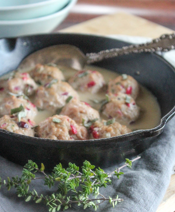 Turkey meatballs in gravy in a pan with a serving spoon