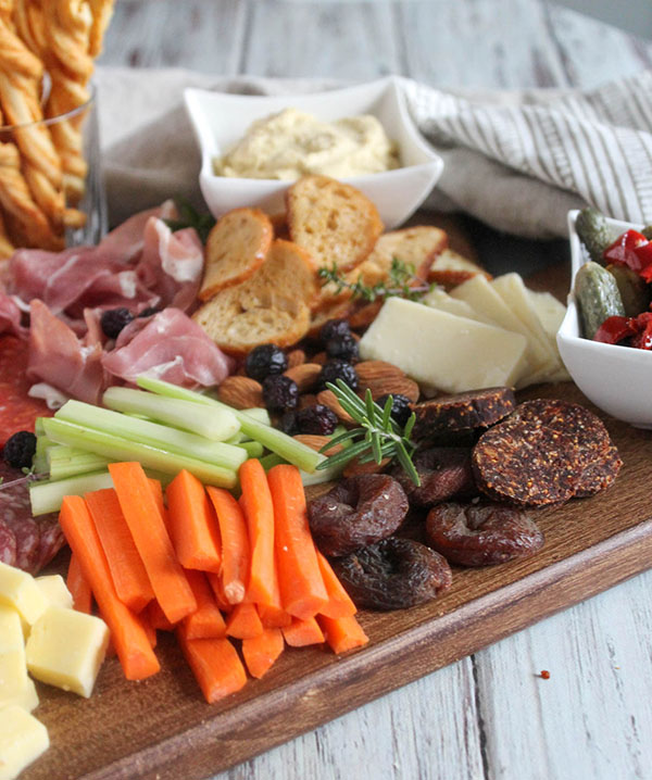 carrots, celery, dried apricots and fig salami on a board