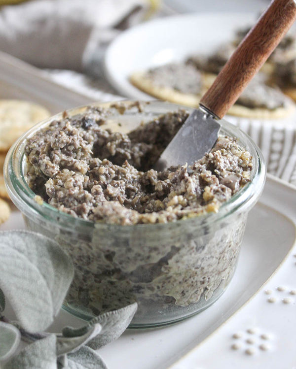 A close up view of vegan mushroom pate in a jar with a spreading knife