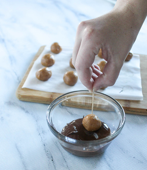 Peanut butter ball being dipped into chocolate