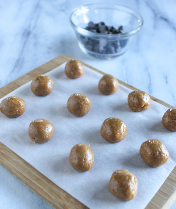 Peanut butter mixture rolled into balls on a board