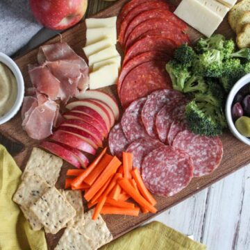 An overhead view of a charcuterie board filled with salami, apples, cheese, olives broccoli, carrots and crackers