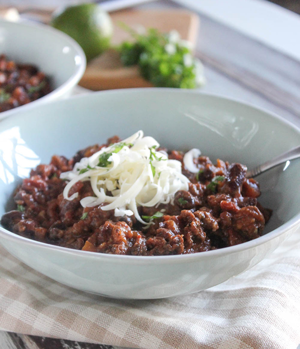 a close up photo of easy chili in a bowl topped with cheese