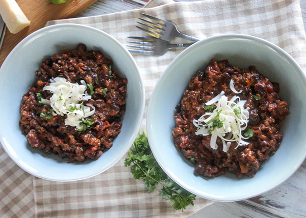 an overhead view of two bowls of chili with shredded cheese