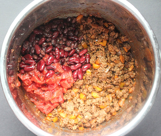 cooked ground beef, beans tomatoes and peppers in a pressure cooker before they are cooked