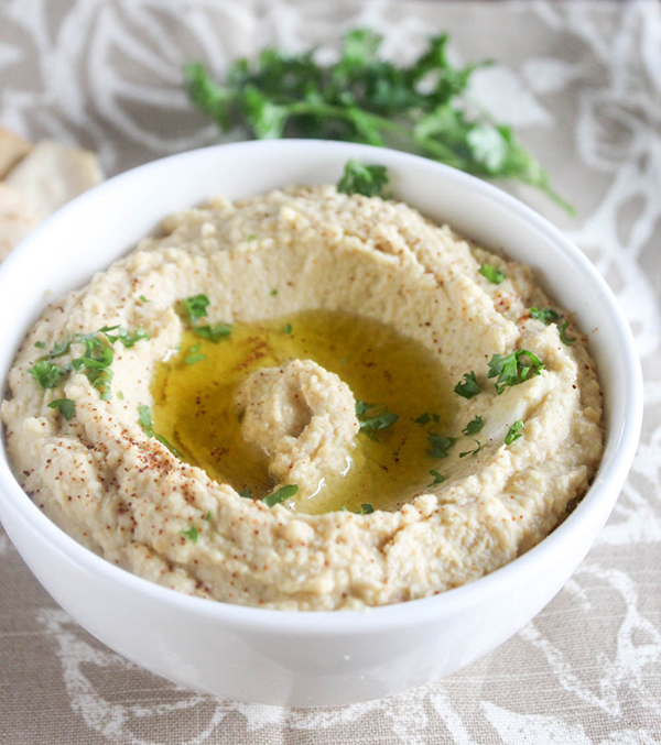 A close up picture of classic hummus in a white bowl