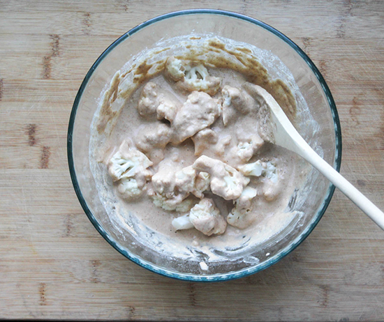 cauliflower florets in a mixing bowl with the batter