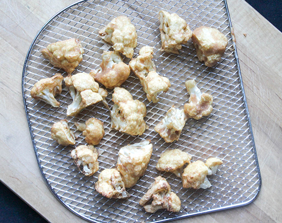 Battered and baked cauliflower florets on a baking tray for the air fryer