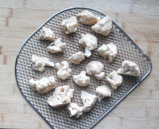 cauliflower florets covered in batter ready to be baked on an air fryer tray