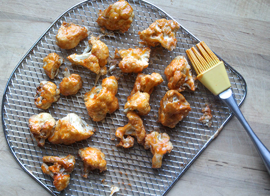 spicy buffalo cauliflower bites on an air fryer baking tray covered with sauce