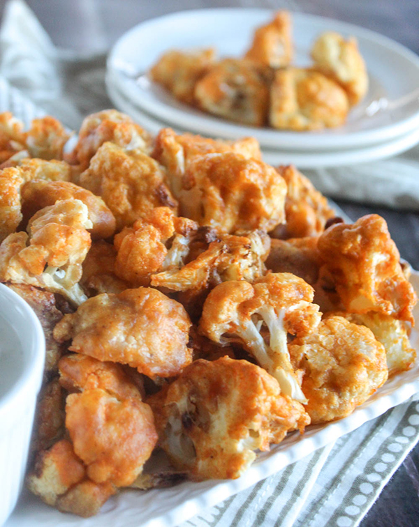 buffalo cauliflower bites on a tray with a serving plate in the background