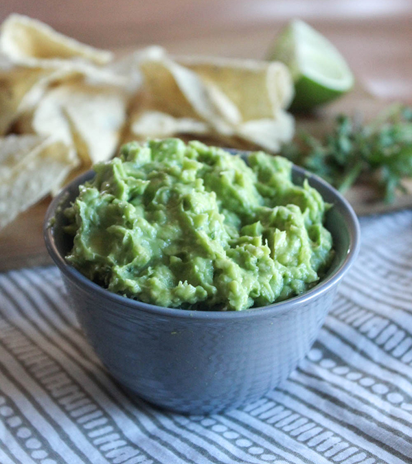 guacamole in a grey bowl with chips in the background