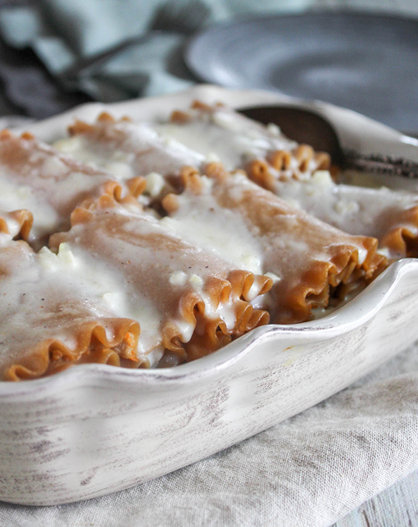 The cooked lasagna roll ups in a baking pan