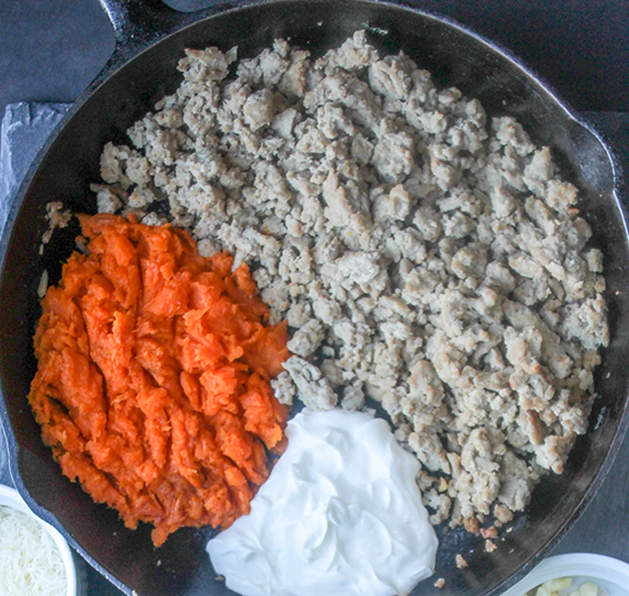 Ground turkey, sweet potato and yogurt in a skillet