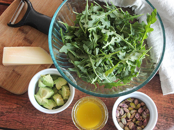 THe ingredients: arugula, avocados, lemon dressing, pistachios and parmesan cheese