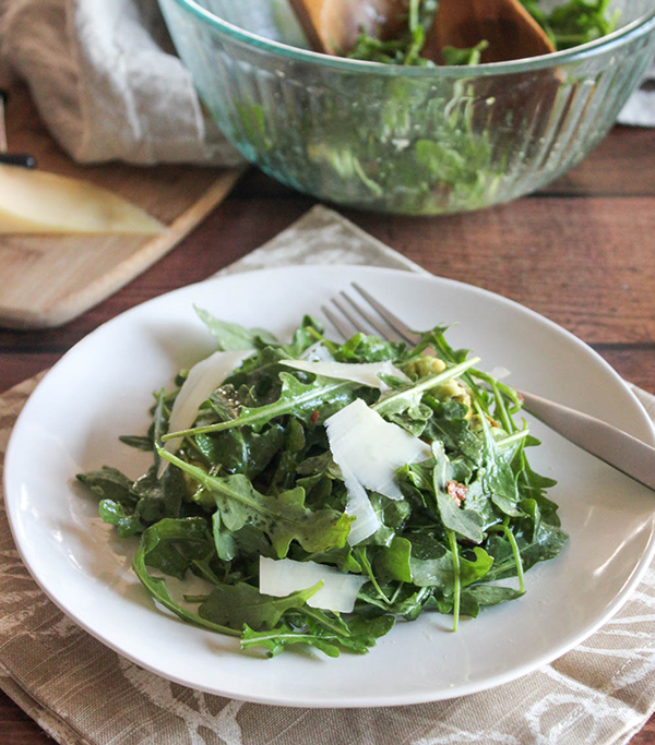 Arugula salad on a white plate with shredded cheese